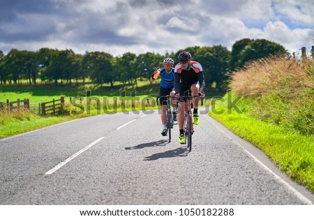 Two cyclists on a cycling tour on country roadson a sunny day in the UK.
