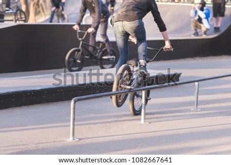 Two cyclists on BMX bikes do tricks in a park skate. Bike skater slides on BMX by perel. Training of tricks on BMX Stock fotó ©