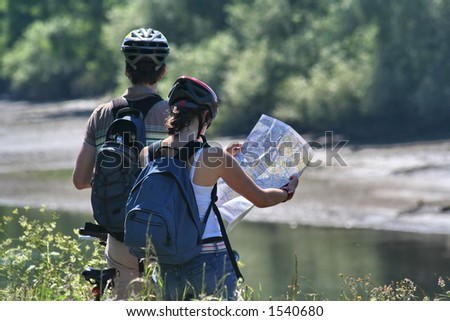Two cyclists on the Thames river bank reading a map