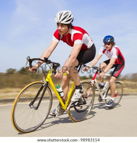Two cyclists sprinting past the camera at high speed