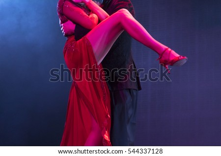 Two dancers performing tango in blue and red stage lights. Close up view of legs, no faces.