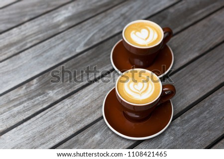 Two dark red cups of cappuccino with the heart shape latte-art on wood background Foto stock ©