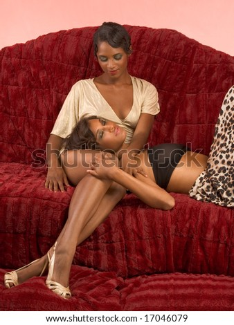 Two dark skinned sensual female lovers petting on couch (retro style)