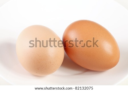 Two darker and lighter brown colored eggs