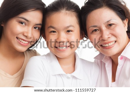 Two daughters with mother looking at camera - stock photo