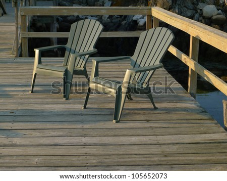 Two deck chairs on a dock at sunset
