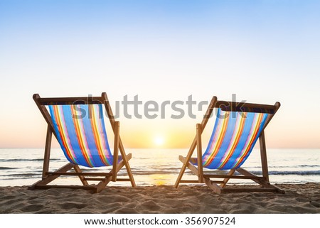 Two deck chairs on a tropical sandy beach with beautiful colorful sunset #356907524