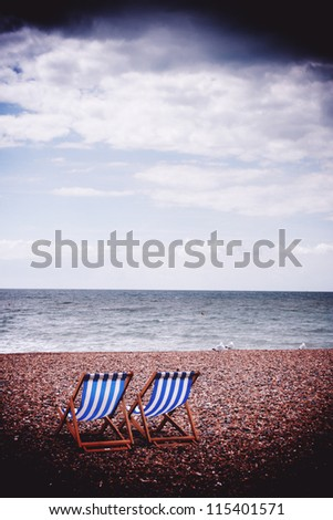 Two deck chairs on Brighton beach - stock photo