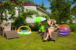 Two deckchairs and a young girl on a green lawn in the courtyard of a country house. The concept of summer holidays in 2020 is due to the worldwide spread of COVID-19.