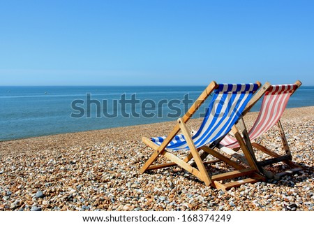 two deckchairs on a pebbled beach, facing out to sea #168374249