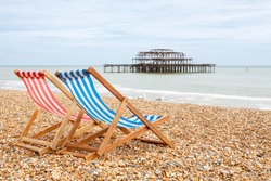 Two deckhairs on Brighton beach with West Pier behind. Brighton, East Sussex, England