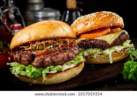 Two delicious beef burgers with salad trimmings, one a cheeseburger and the other with ham and ketchup on a dark wooden board in a close up view