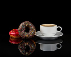 Two delicious donuts and a white coffee cup with coffee on a black background with reflection