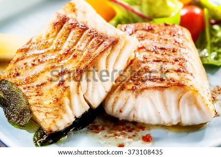 Two delicious fillets of marinated grilled or oven baked pollock or coalfish served with a fresh salad, close up view showing the texture