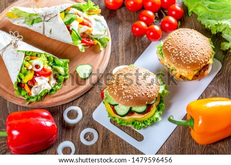 Two delicious hamburgers and cheeseburgers with different vegetables in a circle. American calorie background. #1479596456