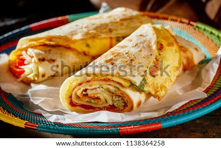 Two delicious indigenous Ugandan Rolex Rolls made with egg omelette and diced fresh vegetables rolled in a chapati or roti on a colorful woven basket