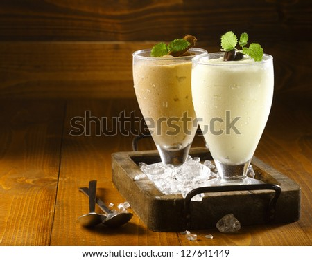 Two delicious thick icecream milkshakes garnished with chocolate and mint and served in tall chilled glasses on a small old wooden tray