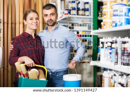 Two designer are holding paint and all instruments for redecorate room in the store. Focus on man
