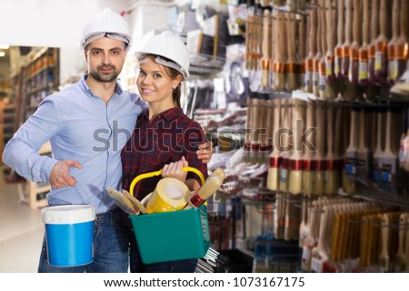 Two designer in helmet are holding paint and all instruments for redecorate room in the store