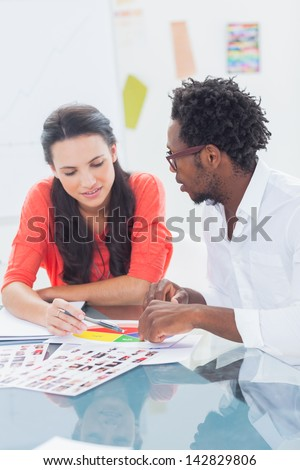 Two designers working together pointing at a colour wheel - stock photo