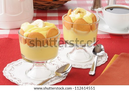 Two dessert cups of vanilla pudding and cookies