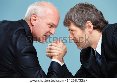 Two determined businessmen going head to head in a challenge for supremacy staring into each others eyes and arm wrestling