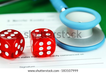 Two dice placed on a a doctors medical certificate pad next to his light blue stethoscope, asking the question do you gamble with your health care?