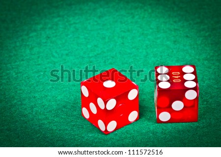 Two dices with seven over a green table