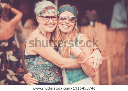 Two different ages females friends hug and stay in love together with smile and fun - cheerful different ages caucasian people - mother and daughter - happy  hippy people in vintage color filter
