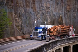 Two different models of classic big rigs semi trucks transporting logs and another commercial cargo moving towards each other met on the bridge over the abyss in Columbia Gorge, Washington