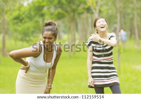 Two different races woman laughing, black and asian.