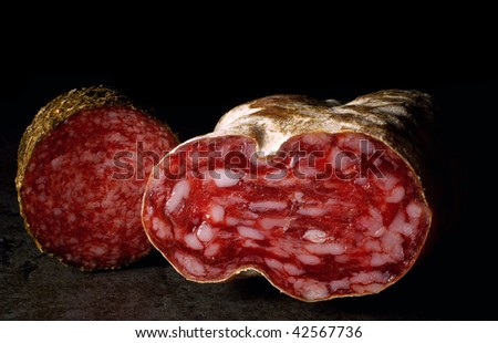 Two different salamis on a black background