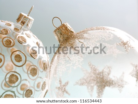 Two differently decorated christmas bar balls leaning on each other on a blue background. - stock photo