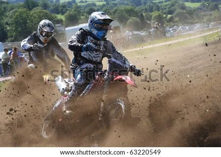 Dirt Bikes battle the corner in a cloud of mud : Shutterstock