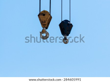Two dirty industrial crane hoist hooks and pulleys hanging by steel cables on pale blue sky.