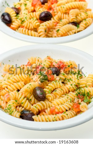 Two dish of IFusilli with cheese, fresh tomatoes and olives. Isolated on white.