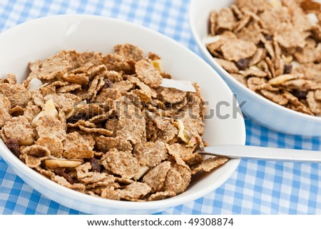 Two dishes of delicious bran flakes on a chequered cloth