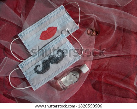 Two disposable face masks with a mustache and lips painted on them, wedding rings and antiseptic are on red background. The concept of wedding ceremonies during a pandemic of coronavirus COVID-19