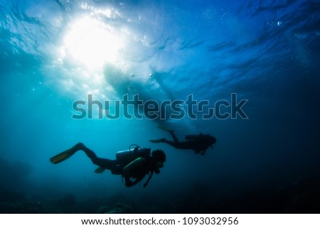 Two divers swim underwater in a tropical sea with a silhouette of a boat over them. Philippines