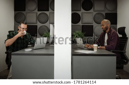 Two diverse businessman working on laptops in separate cubicles while physical distancing in their office