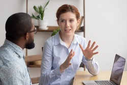 Two diverse businesspeople chatting sitting behind laptop in office. Excited caucasian female sharing ideas or startup business plan with black male coworker. Informal conversation, work break concept
