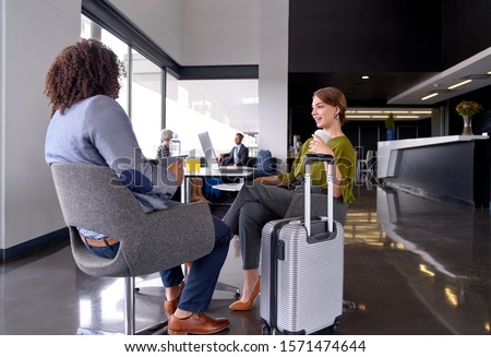 Two diverse fashionable business people meeting and talking in h stock photo