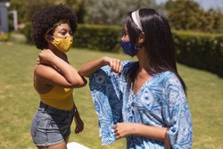 Two diverse female friends wearing face masks bumping elbows at a pool party. Health and hygiene precautions while hanging out and relaxing outdoors in summer during coronavirus covid 19 pandemic.