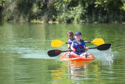 Two diverse little boys kayaking down a beautiful river