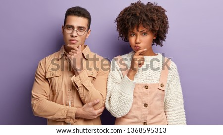 Two diverse partners hold chin, look thoughtfully, have indecisive expression, thinks over how to develop plan, wear casual clothes, stand shoulder to shoulder against purple wall. Multiethnic couple