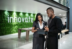 Two diverse young African businesspeople talking together over a digital tablet while standing in the lobby of a modern office