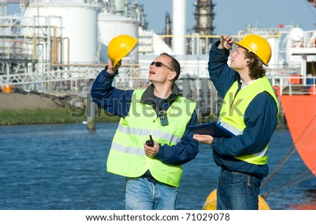Two dock workers at inspection, looking up.