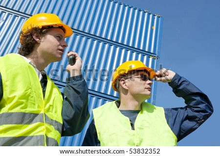 Two dock workers in safety clothing supervising and giving instructions using a walkie-talkie.