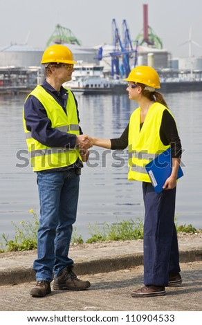 Two dockers, a man and a woman shaking hands in an industrial harbor, wearing the necessary safety gear
