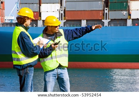 Two Dockers at work in an industrial harbor, giving instructions, and writing them down.
